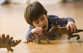 Mixed race boy playing with dinosaur toys
